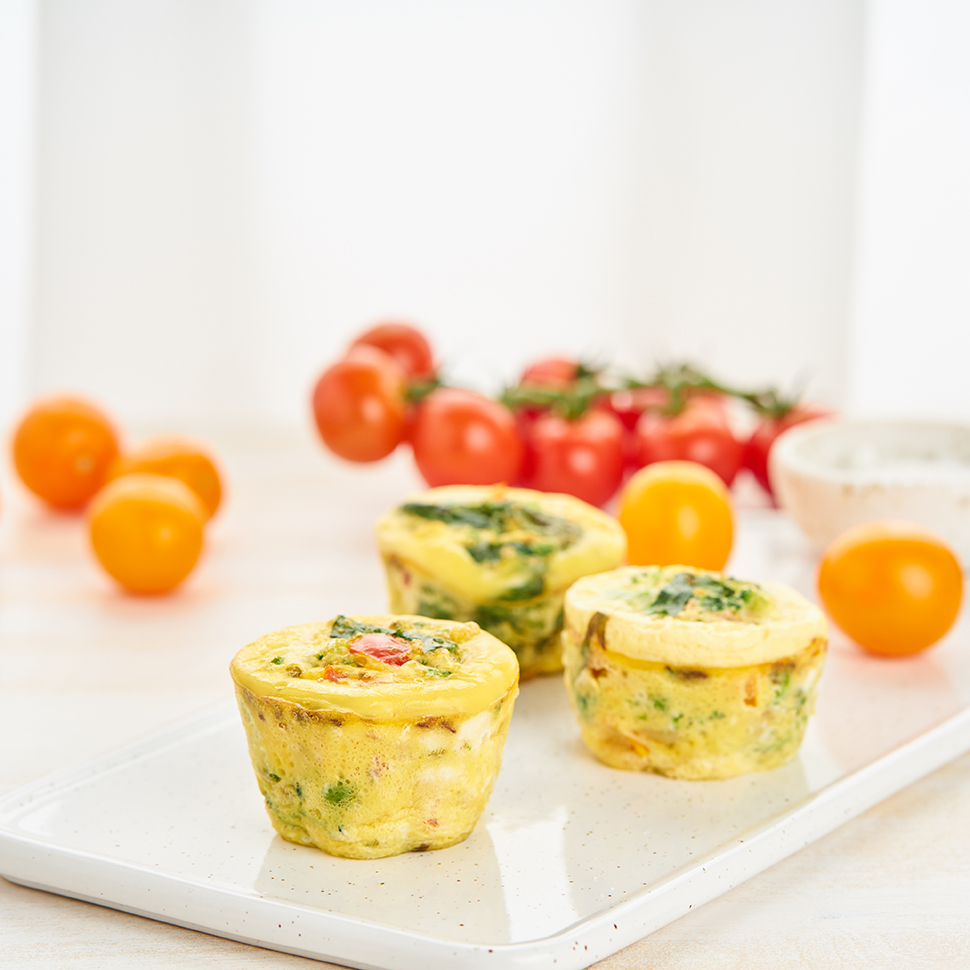 Baked-Egg-Bites-Recipe-On-A-White-Plate-With-Cherry-on-Vine-Tomatoes-in-the-Background