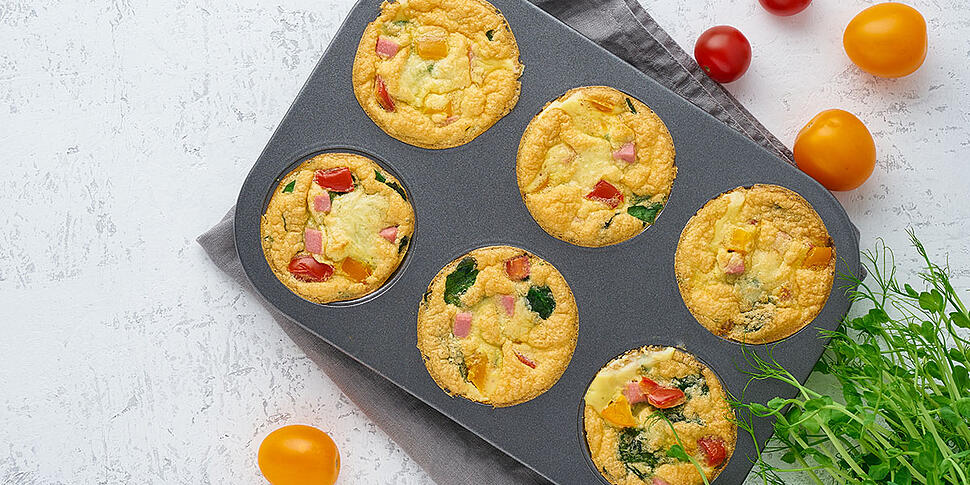 Baked Egg Bites on a muffin pan on top of a white background