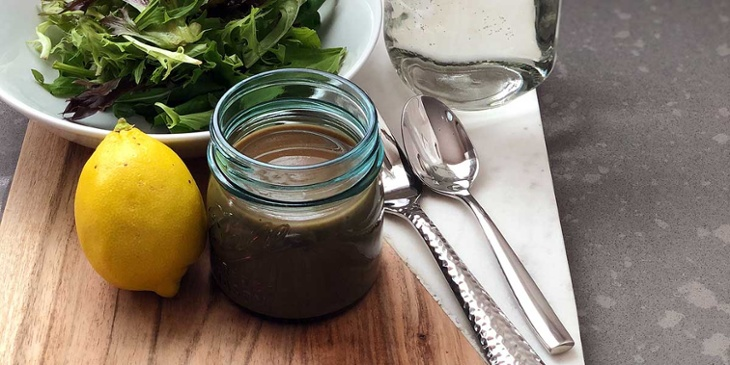 Balsamic Vinaigrette plated on a round mason jar on top of a wood and marble tray next to silverware and fresh produce