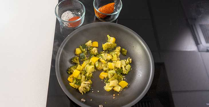 Garlic and vegetables being sauteed in a nonstick pan next to spices and soyrizo