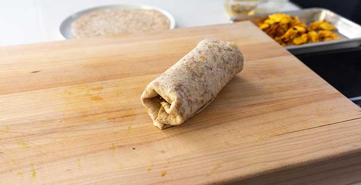 Folded burrito placed on a wooden cutting board