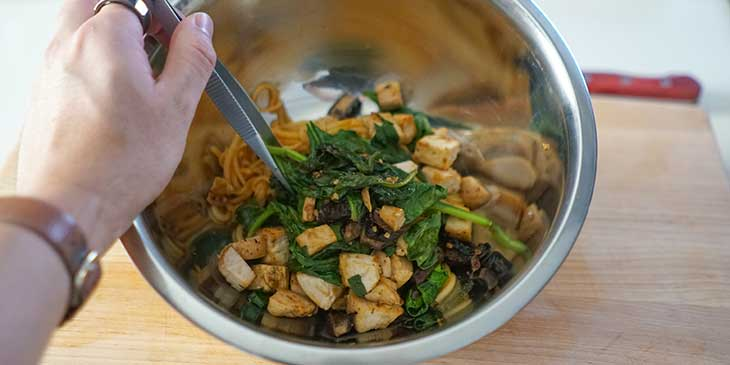 All chicken and mushroom sauced-noodle ingredients being mixed on a stainless steel bowl