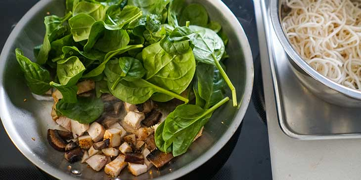chicken mushrooms and spinach being cooked in a large stainless steel pan