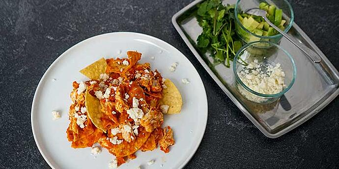 Chilaquiles Chicken Recipe plated on a white porcelain plate with garnishes on the side