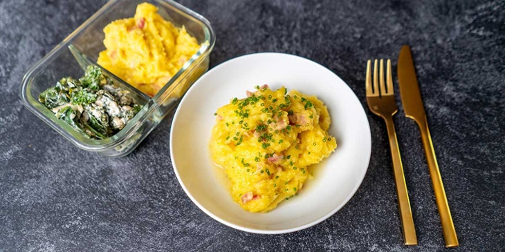 Creamy Bacon and Spaghetti Squash plated on a white bowl and glass container next to golden silverware