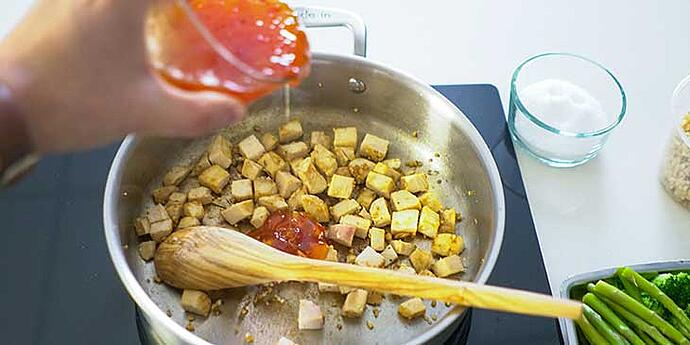 Easy Sweet and Sour Chicken Recipe being cooked on a fry pan and sweet and sour sauce being poured over