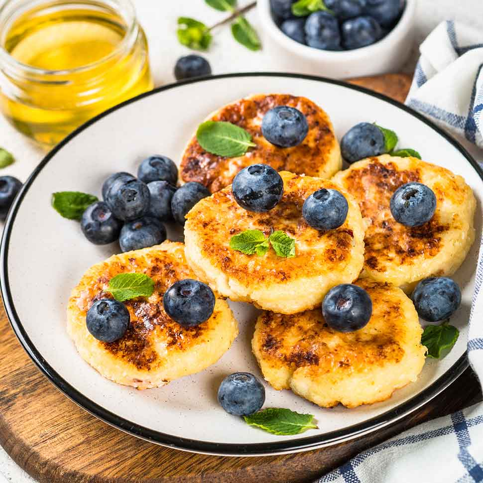 Fluffy-Keto-Pancakes-on-a-white-plate-served-with-blue-berries-and