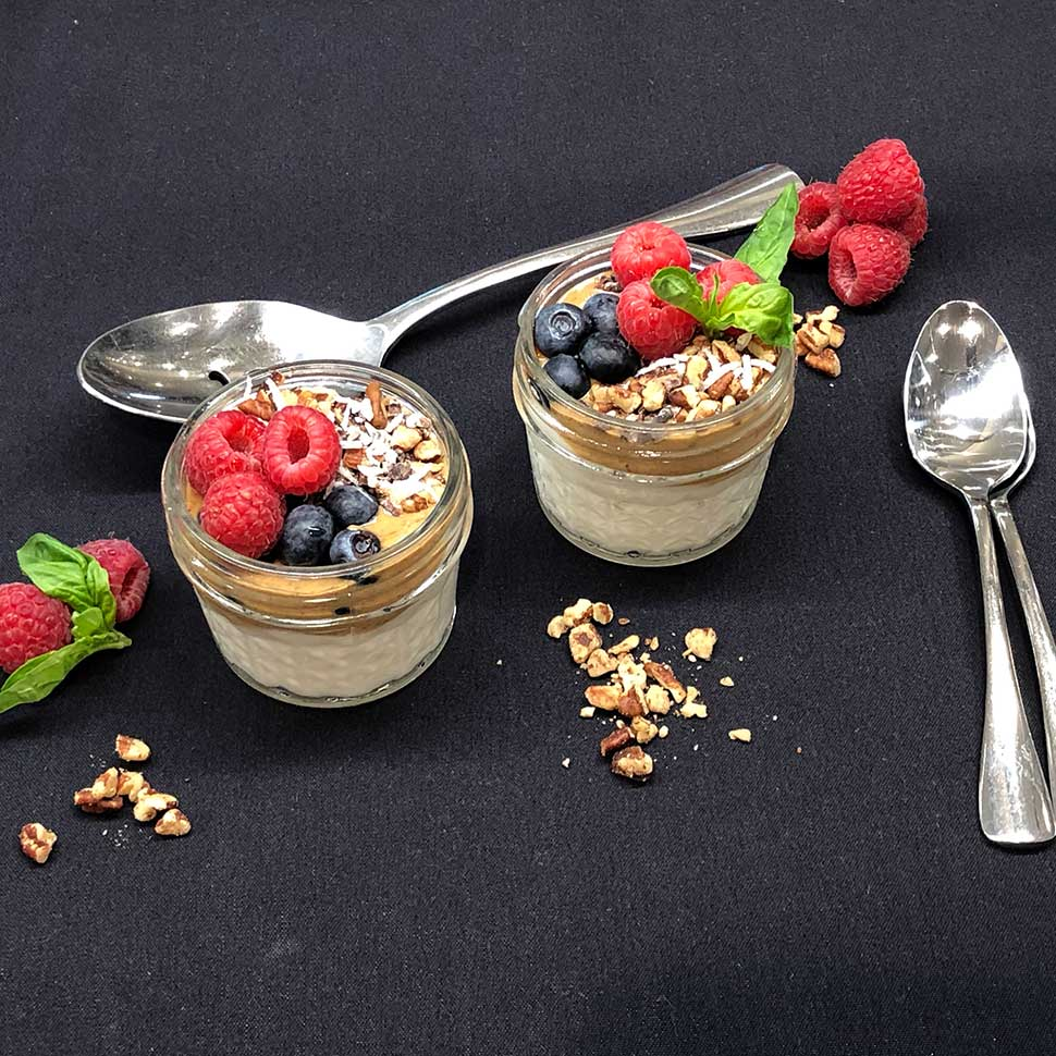 Fully-Loaded-Keto-Breakfast-Parfait-in-Jars-with-Berries-and-Nut-Crust-on-a-Black-Background