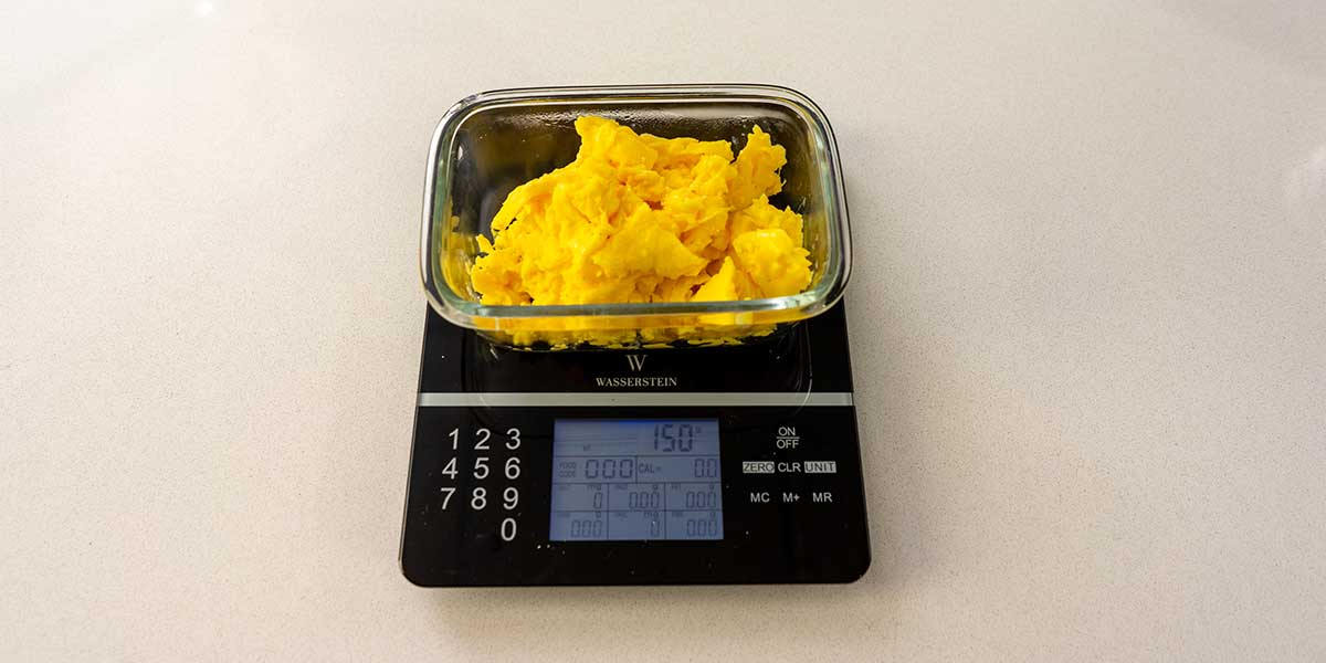 Scrambled eggs portioned into glass rectangular meal prep containers on a black food scale
