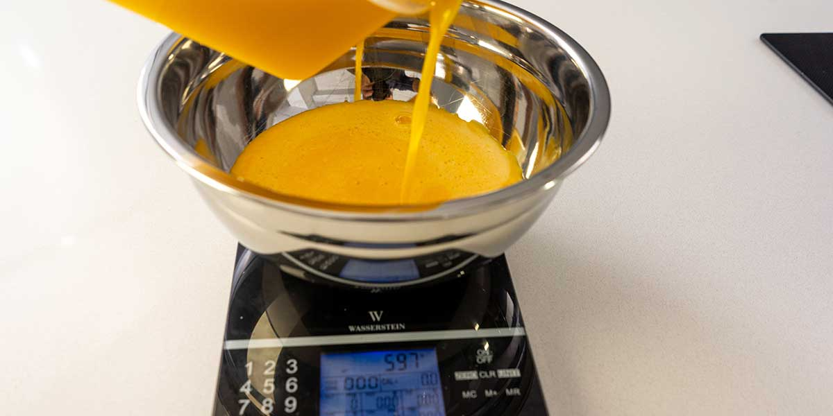 Weighing scrambled liquid eggs on a black food scale
