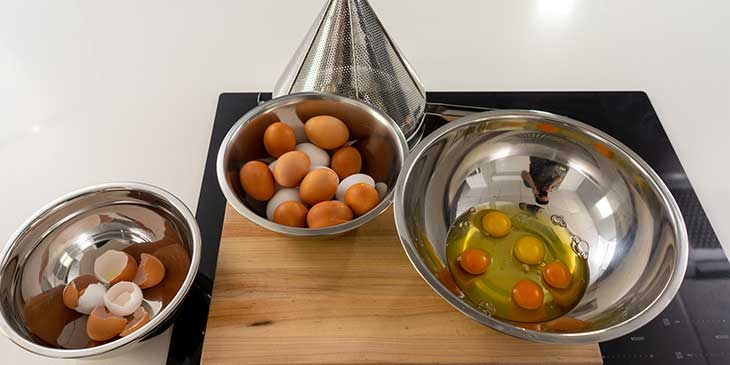 Cracking egg station set to crack eggs for meal prep with different bowls on top of a cutting board