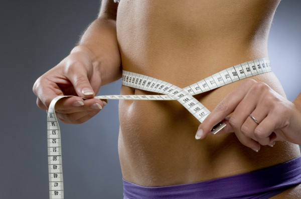 women measuring waist circumference to estimate her body fat loss