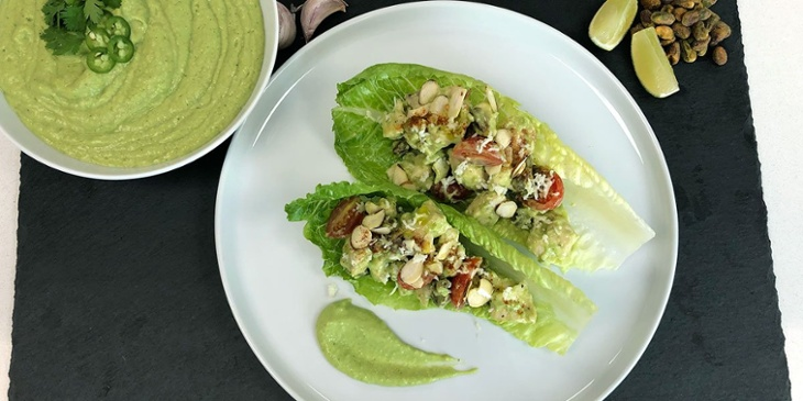 Keto guacatilllo chicken salad wrap plated on a white round plate placed on top of a black slab next to a green guacatillo sauce bowl