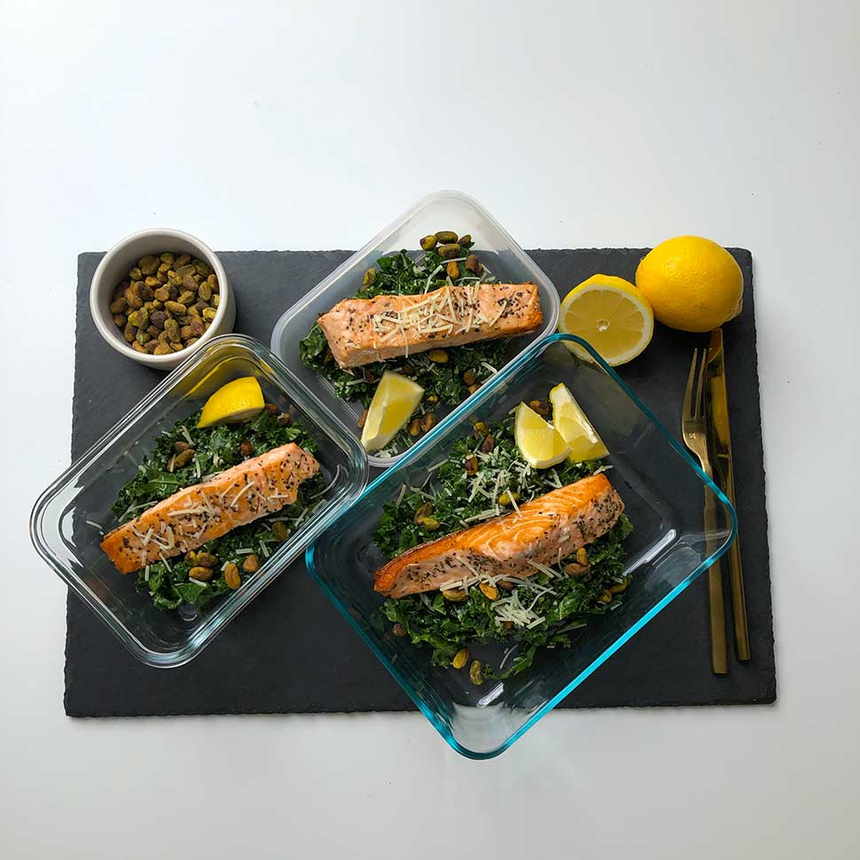 keto-salmon-baked-on-a-lemon-parm-kale-salad-with-a-black-background-in-meal-prep-containers
