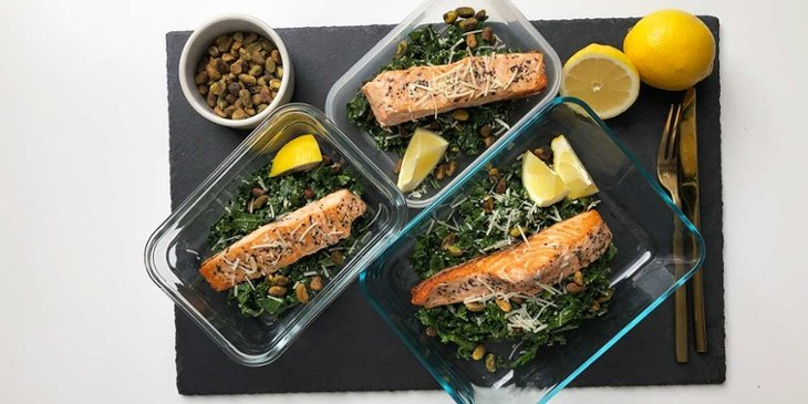 Keto salmon on a keto parm kale salad with pistachios plated on glass meal prep containers on top of a black stone slab