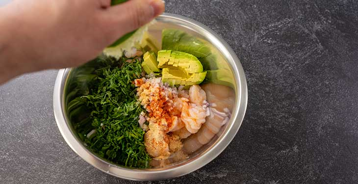 Mixed ingredients for keto shrimp avocado salad in a stainless steel bowl
