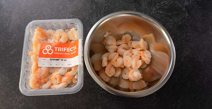 Trifecta meal delivery shrimp and cooked shrimp on a stainless steel bowl