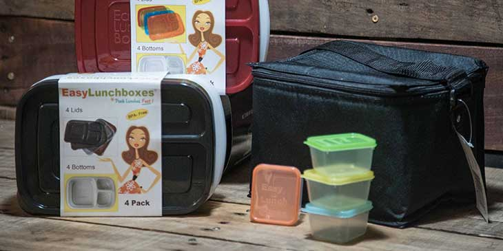 Various sized  plastic meal prep containers next to a black lunch box on a wooden background