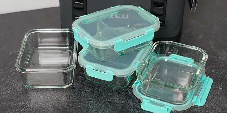 Glass meal prep containers set next to a yeti meal prep bag on a black table