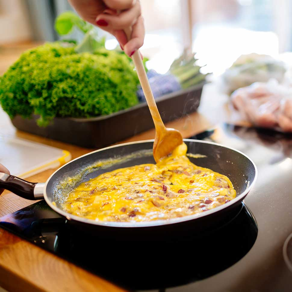 Meal-Prep-Scrambled-Eggs-On-a-Non-stick-pan-with-a-wooden-spoon