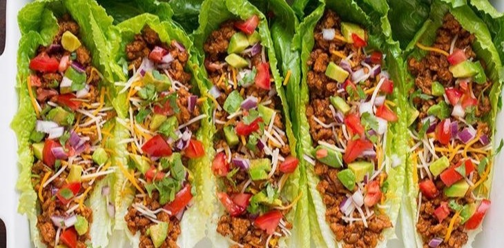 five colorful steak and avocado lettuce wraps placed side to side