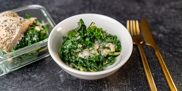 Paleo-Aromatic Greens with coconut Recipe plated on a white bowl and meal prep container next to golden utensils on a black backdrop