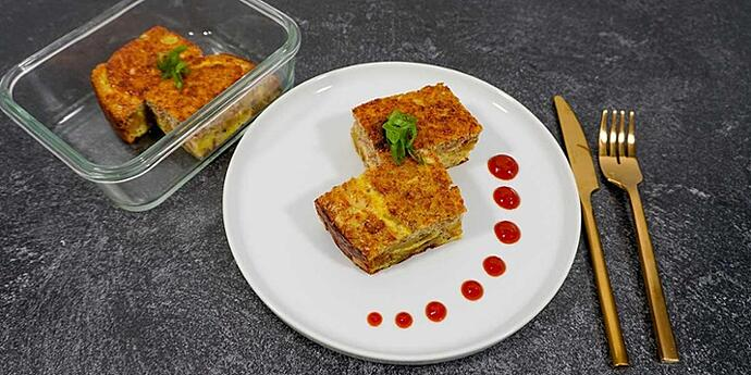 Paleo Breakfast Egg and Sausage Casserole plated on a white plate and meal prep containers with fresh herbs next to golden silverware