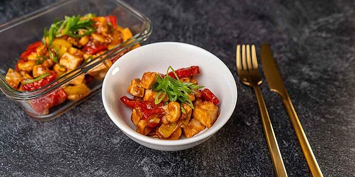Paleo Cashew Chicken Recipe plated on a white bowl and meal prep container next to golden silverware