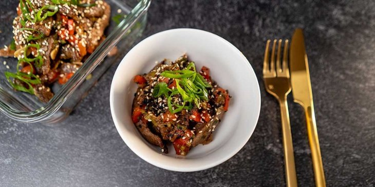 Paleo Mongolian Beef Recipe plated on a small white bowl and on a clear glass meal prep container next to golden utensils on a black backdrop