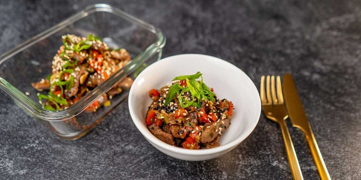 Paleo-Mongolian-Beef-Recipe plated on a white bowl and glass meal prep container next to golden silverware