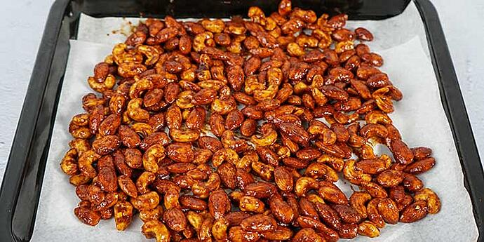 Paleo Roasted Spiced Nuts Recipe transfer seasoned nuts to a baking sheet