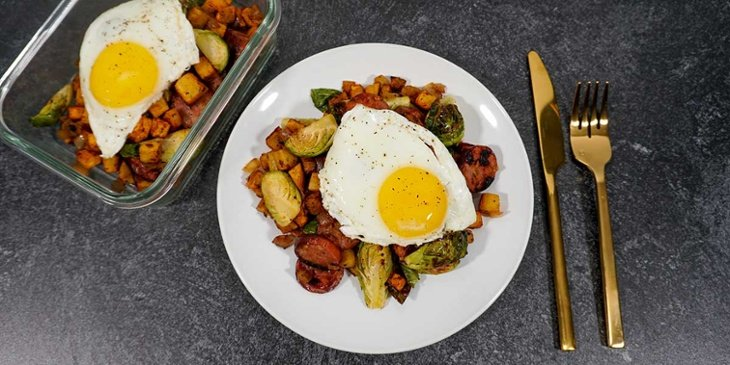 Paleo Sweet Potato Hash with Sausage Egg plated on a white plate and meal prep container on black background next to golden silverware