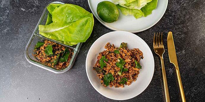 Paleo Thai Turkey Larb Recipe plated on a white bowl and glass meal prep container with a side of lettuce and lime next to golden silverware