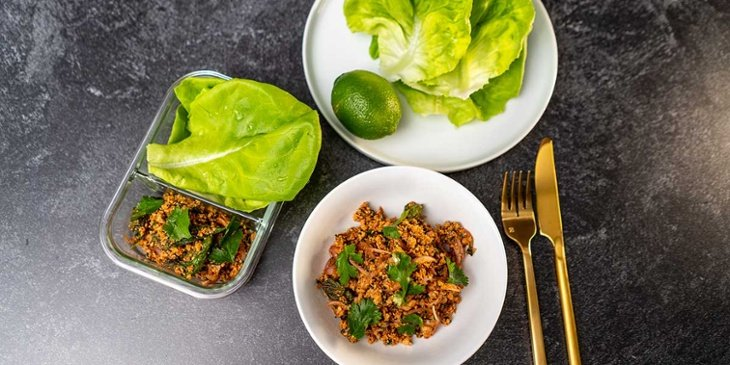 Paleo thai turkey larb recipe plated on a white bowl next to golden silverware and fresh lettuce on a round white plate