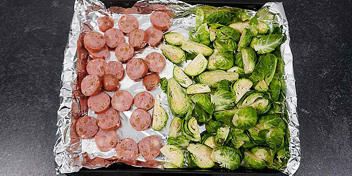 Cut brussels and sausage and place in sheet tray