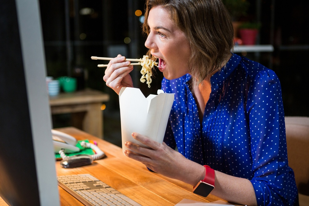 woman at computer eating fat carbs noodles diet weight loss