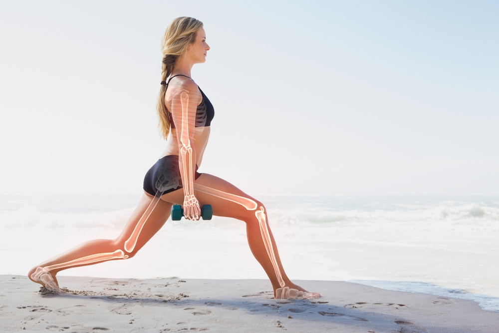 woman exercising weight bearing activity on beach for bone density