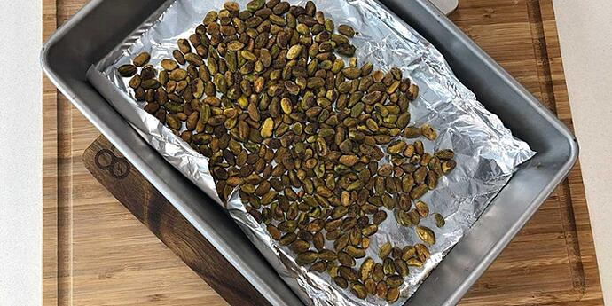 Toasted pistacchio nuts on a foiled-lined baking sheet placed on top of a wooden cutting board