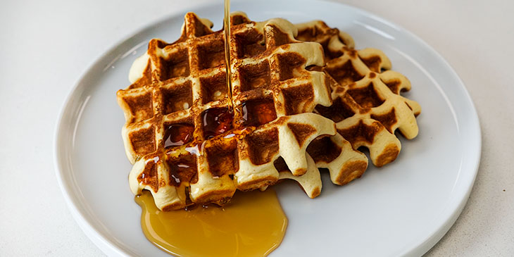 Protein waffles with maple syrup on a white plate