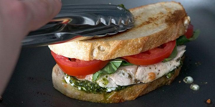 cooking chicken pesto sandwich in skillet