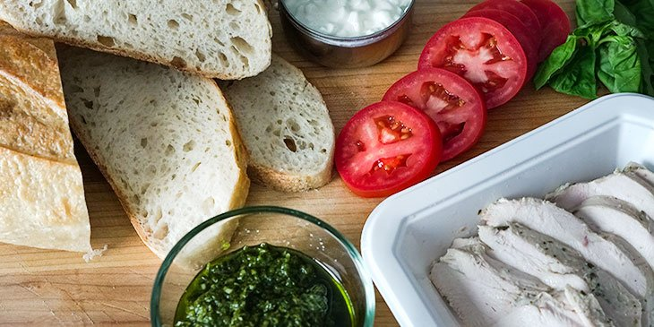 ingredients for pesto chicken sandwich recipe on cutting board
