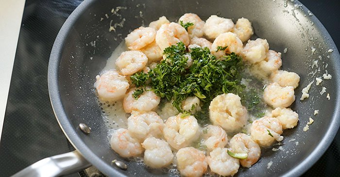 sauteing garlic shrimp in a pan with herbs