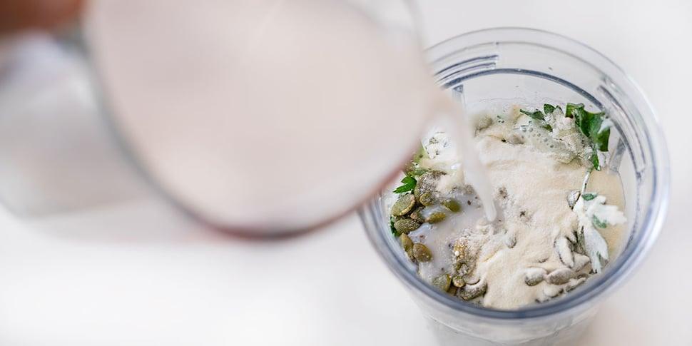 adding milk to keto green smoothie for keto meal prep