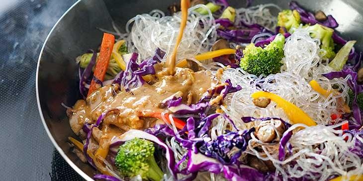 adding sauce to vegan pad thai in wok