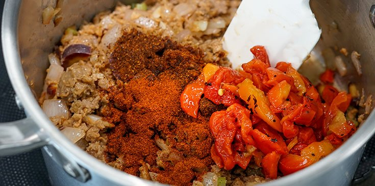 adding spices and peppers to vegetarian chili recipe
