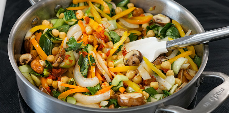 adding vegan red curry to saute vegetables