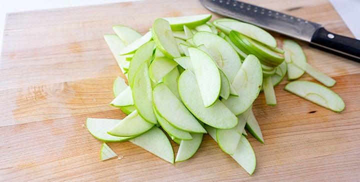 sliced apples for apple crisp recipe on cutting board