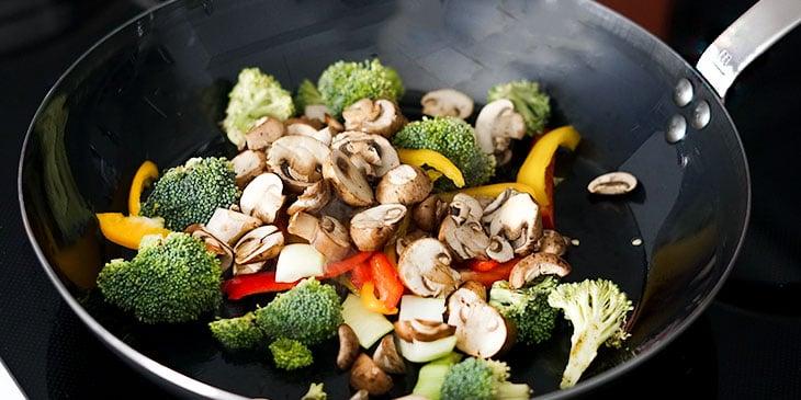 stir frying vegetables in wok
