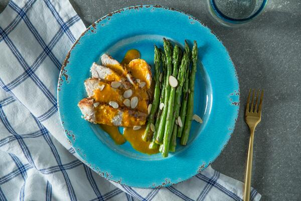 Paleo meal on a plate with tangerine chicken and asparagus