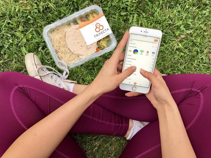 woman tracking food intake of turkey burger veggies rice and calories for weight loss using trifecta app